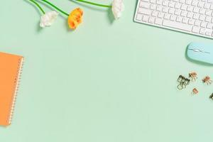 Minimal work space - Creative flat lay photo of workspace desk. Top view office desk with keyboard, mouse and notebook on pastel green color background. Top view with copy space, flat lay photography.