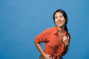 Retrato de una joven asiática con expresión positiva, una amplia sonrisa, vestida con ropa casual sobre fondo azul. feliz adorable mujer alegre se regocija con el éxito. concepto de expresión facial. foto