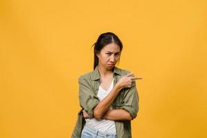 joven asiática muestra algo sorprendente en el espacio en blanco con expresión negativa, gritos emocionados, llorando enojado emocional mirando a cámara aislada sobre fondo amarillo. concepto de expresión facial. foto