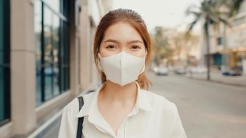 Successful young Asia businesswoman in fashion office clothes wear medical face mask smiling and looking at camera while happy standing alone outdoors in urban modern city. Business on the go concept. photo