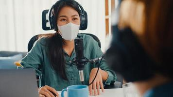 Asia girl radio host record podcast use microphone wear headphone interview guest content wear mask protect virus conversation talk and listen in her room. Podcast from home, coronavirus quarantine. photo