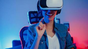 feliz chica asiática usa gafas de realidad virtual gafas auriculares siente sorpresa programa de juego real en su estudio de neón en casa por la noche, mujer joven toca el aire la experiencia de realidad virtual, actividad de cuarentena en casa. foto