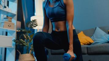 Young Asia lady in sportswear doing squat with dumbbells in outstretched arms exercise working out in living room at home at night. Sport and recreation activity, quarantine for corona virus concept. photo