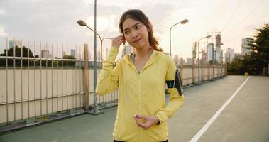 Beautiful young Asia athlete lady exercises using smartphone for listen to music while running in urban environment. Korean teen girl wearing sports clothes on walkway bridge in early morning. photo