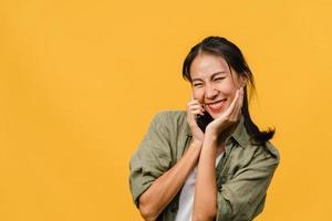 Jovencita asiática habla por teléfono con expresión positiva, sonríe ampliamente, vestida con ropa informal sintiendo felicidad y parada aislada sobre fondo amarillo. feliz adorable mujer alegre se regocija con el éxito. foto