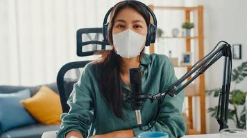Teenager Asia girl record podcast use headphones and microphone wear mask protect virus look at camera talk in her room. Female podcaster make audio podcast from her home studio, Stay at home concept. photo