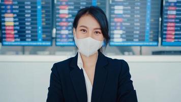 chica de negocios asiática usa mascarilla pararse frente a la tabla de vuelo mostrar tiempo mirar a la cámara del aeropuerto internacional. pandemia de covid de viajeros de negocios, distanciamiento social de viajeros de negocios, concepto de viajes de negocios. foto