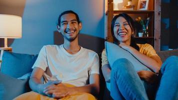 La pareja romántica de Asia, el hombre y la mujer, sonríen y se ríen, se acuestan en el sofá de la sala de estar por la noche, ven una película de comedia en la televisión juntos en casa. estilo de vida familiar de pareja casada, concepto de estancia en casa. foto