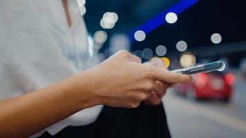 Close-up asiática chica de negocios de pie fuera de la terminal mirar teléfono inteligente comprobar reserva de hotel esperar coche en el aeropuerto nacional. pandemia de covid viajero de negocios, concepto de distanciamiento social de viajes de negocios. foto