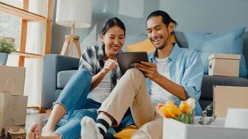 Feliz pareja joven y atractiva asiática hombre y mujer usan tableta muebles de compras en línea decoran casa con paquete de cartón mudanza en casa nueva. joven casado asiático mudanza comprador casa concepto en línea. foto