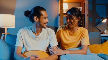 Feliz pareja de jóvenes asiáticos hombre y mujer mirando a la cámara sonríen y alegres en la videollamada en línea por la noche en la sala de estar en casa, quedarse en casa en cuarentena, vida matrimonial, concepto de distanciamiento social. foto