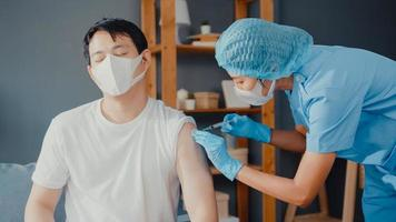 Young Asia lady nurse giving Covid-19 or flu antivirus vaccine shot to male patient wear face mask protection from virus disease sit on couch in living room at house. Vaccination concept. photo