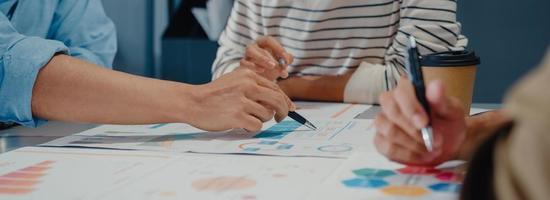 jóvenes empresarios asiáticos reunidos intercambiando ideas sobre nuevas ideas sobre proyectos y socios trabajando juntos planificar la estrategia de éxito disfrutan del trabajo en equipo en la oficina. Fondo de banner panorámico con espacio de copia. foto