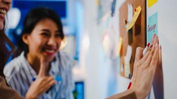 Grupo de jóvenes empresarios asiáticos discutiendo reunión de intercambio de ideas de negocios trabajando juntos compartiendo datos y escribiendo pizarra en la pared con una nota adhesiva en la oficina de noche. concepto de trabajo en equipo de compañero de trabajo. foto