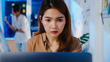 Happy Asia businesswoman social distancing in new normal situation for virus prevention while using laptop online business overtime back at work in office night. Life and work after coronavirus. photo