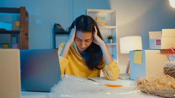 Young Asia businesswoman look around room full of product stuff and parcel box feel stress and upset with bad sell in home office at night. Small business owner, online market delivery concept. photo