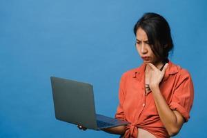Jovencita asiática usando laptop con expresión negativa, gritando emocionado, llorando emocionalmente enojado en ropa casual y parado aislado sobre fondo azul con espacio de copia en blanco. concepto de expresión facial. foto