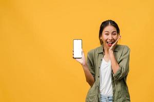 Joven asiática muestra la pantalla vacía del teléfono inteligente con expresión positiva, sonríe ampliamente, vestida con ropa casual sintiendo felicidad sobre fondo amarillo. teléfono móvil con pantalla en blanco en mano femenina. foto