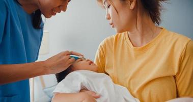 joven pediatra de asia adjuntar el gel antipirético en la frente del bebé visita del paciente al médico con la madre en la sala de estar de la casa. seguro de atención médica, tratamiento y concepto de salud. foto