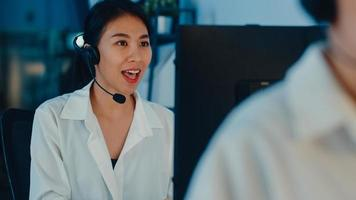 Millennial Asia young call center team or customer support service executive using computer and microphone headset working technical support in late night office. Telemarketing or sales job concept. photo