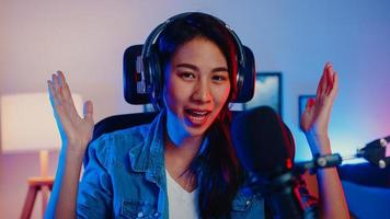 Happy asia girl blogger music influencer looking at camera broadcast record wear headphone online live talk in microphone with audience in living room home studio at night. Content creator concept. photo