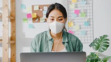 Asia empresaria vistiendo una mascarilla médica usando una computadora portátil hable con sus colegas sobre el plan en una videollamada mientras trabaja desde su casa en la sala de estar. distanciamiento social, cuarentena para la prevención del coronavirus. foto