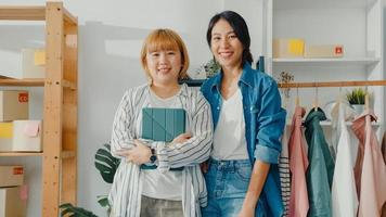 Portrait of young Asia women fashion designer feeling happy smile, arms crossed and looking to camera while working clothing store in home office. Small business owner, online market delivery concept. photo