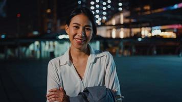 Successful young Asia businesswoman in fashion office clothes smiling and looking at camera while happy standing alone outdoors in urban modern city at night. Business on the go and commuter concept. photo