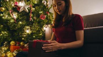 Joven mujer asiática divirtiéndose abriendo caja de regalo de Navidad cerca del árbol de Navidad decorado con adornos en la sala de estar en casa. Feliz noche de navidad y feliz año nuevo festival navideño. foto
