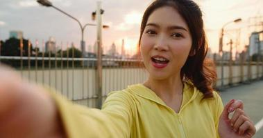 Attractive young Asia athlete influencer lady recording video vlog live streaming on phone upload in social media while exercises in urban city. Sportwoman wearing sports clothes on street in morning. photo