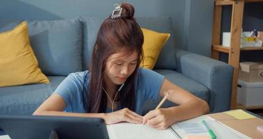 Young Asia girl teenager with casual wear headphones use digital tablet learn online write lecture notebook in living room at house. Isolate education online e-learning coronavirus pandemic concept. photo