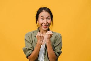 Jovencita asiática con expresión positiva, alegre y emocionante, vestida con ropa informal y mira a cámara sobre fondo amarillo. feliz adorable mujer alegre se regocija con el éxito. concepto de expresión facial. foto