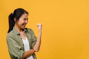 jovencita de asia con expresión positiva, alegre y emocionante, vestida con ropa casual sobre fondo amarillo con espacio vacío. feliz adorable mujer alegre se regocija con el éxito. concepto de expresión facial. foto