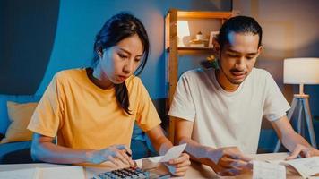 estrés asia pareja hombre y mujer utilizan la calculadora para calcular el presupuesto familiar, las deudas, los gastos durante la crisis económica financiera en casa por la noche. problemas de dinero del matrimonio, concepto de plan de presupuesto familiar. foto