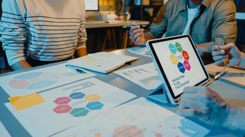 Reunión de empresarios de Asia, análisis de estadísticas, lluvia de ideas y encabezado del equipo mantenga el gráfico de puntos de la tableta y el empleado tome nota en la noche moderna de la oficina en casa. concepto de éxito de la estrategia financiera. foto