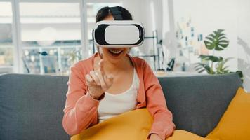 Asian lady wearing headset glasses of virtual reality gesticulating hand sitting on couch in living room at house. Stay at home covid quarantine, Re-imagining Reality, VR technology of future concept. photo
