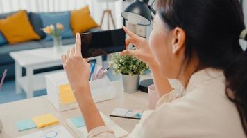 La jovencita asiática usa un teléfono inteligente con pantalla negra en blanco simulada para mostrar texto publicitario mientras trabaja de manera inteligente desde casa en la sala de estar. tecnología chroma key, concepto de diseño de marketing. foto