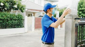 Young postal delivery courier man wear face mask handling food box for send to customer at house and Asian female receive delivered package outdoors. Lifestyle new normal after corona virus concept. photo