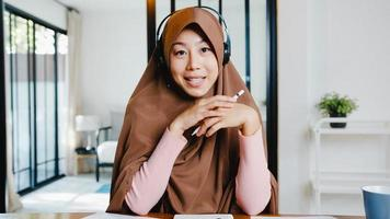 Asia muslim lady wear headphone using computer laptop talk to colleagues about sale report in video call while remotely work from home at living room. Social distancing, quarantine for corona virus. photo