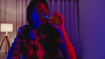 Young Asia lady drinking beer having fun happy moment disco neon night party event online celebration via video call in living room at home. Social distancing, quarantine for coronavirus prevention. photo