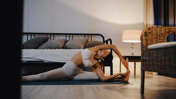 Young Asia lady in sportswear doing yoga exercise working out in living room at home at night. Sport and recreation activity, social distancing, quarantine for corona virus prevention concept. photo