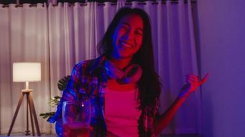 joven asiática bebiendo cerveza divirtiéndose momento feliz discoteca neón noche fiesta evento celebración en línea a través de videollamada en la sala de estar de casa. distanciamiento social, cuarentena para la prevención del coronavirus. foto