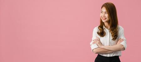 Retrato de joven asiática con expresión positiva, brazos cruzados, sonrisa amplia, vestida con ropa casual y mirando el espacio sobre fondo rosa. Fondo de banner panorámico con espacio de copia. foto