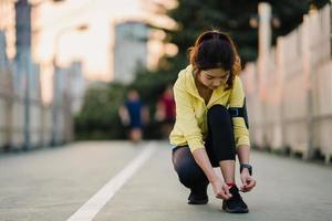 Beautiful young Asia athlete lady exercises tying laces for work out in urban environment. Japanese teen girl wearing sport clothes on walkway bridge in early morning. Lifestyle active sporty in city. photo