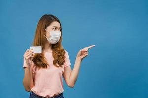 Young Asia lady wearing medical face mask show credit bank card with positive expression, smiles broadly, dressed in casual clothing feeling happiness and stand isolated on blue background. photo