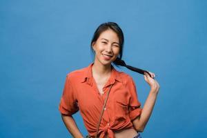 joven asiática con expresión positiva, sonrisa amplia, vestida con ropa informal y mirando a cámara sobre fondo azul. feliz adorable mujer alegre se regocija con el éxito. concepto de expresión facial. foto