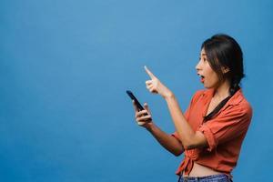 Retrato de una joven asiática que usa un teléfono móvil con una expresión alegre, muestra algo sorprendente en el espacio en blanco en ropa informal y se para aislado sobre fondo azul. concepto de expresión facial. foto