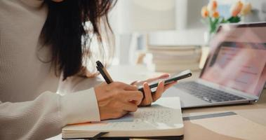 Close-up joven mujer de asia freelance focus chat de teléfono móvil con colegas trabajo finanzas escribiendo en el cuaderno en la sala de estar en casa. alumna aprende en línea en casa, trabaja desde el concepto de hogar. foto