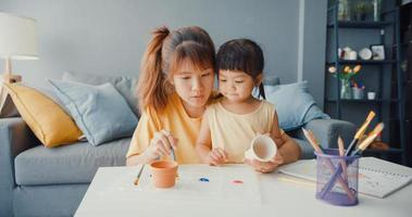 Happy cheerful Asia family mom teach toddler girl paint ceramic pot having fun relax on table in living room at house. Spending time together, Social distance, Quarantine for coronavirus prevention. photo