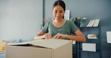 Happy beautiful Asia lady unboxing cardboard delivery package from online marketplace in living room at house. Satisfied shopper in internet unboxing goods, Online shopping and delivery concept. photo